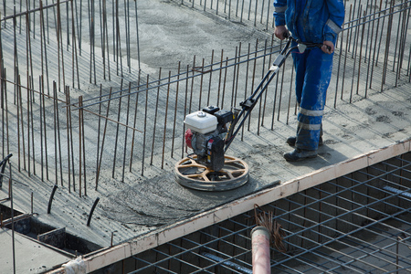 Photo pour Construction worker produces the grout and finish wet concrete with a special tool. Float blades. For smoothing and polishing concrete, concrete floors. - image libre de droit