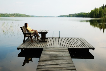 Photo pour Woman is sitting in the wooden armchair. She is resting on the planked platform near quiet lake. - image libre de droit