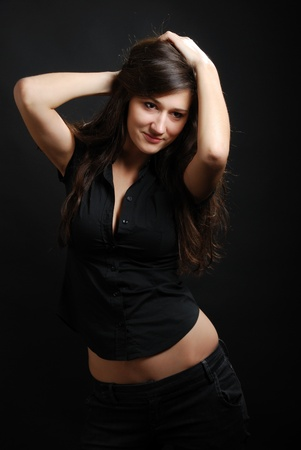 Teenage girl is titivating herself up. Young woman is smoothing her dark long hair. Her face, belly and hands are seen quite well. Her pretty belly aren't covered with black jacket.