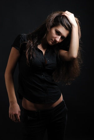 Teenage girl is titivating herself up. Young woman is smoothing her dark long hair. Her face, belly and hands are seen quite well. Her pretty belly are not covered with black jacket.