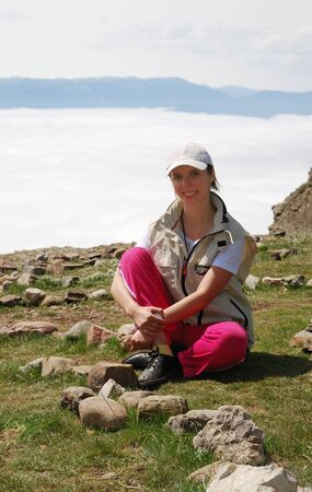 Young woman is sitting on the top of mountain. There is dence field of white clouds behind her.