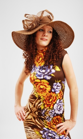 A curly young woman in the colorful dress and the hat wide-brimmed.