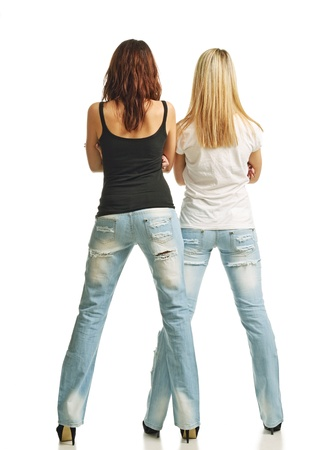 Two young women are standing back  Their legs are planted apart on high heels  They are wearing jeans, tank top and T-shirt