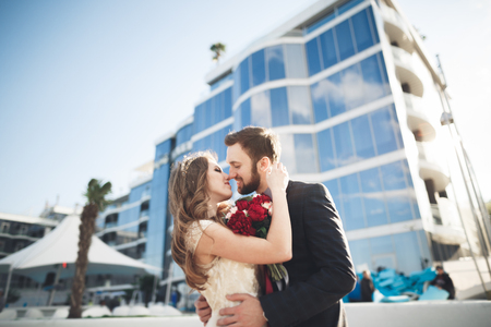 Elegant beautiful couple posing near modern glass building.