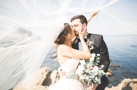 Foto de Wedding couple, groom, bride with bouquet posing near sea and blue sky - Imagen libre de derechos