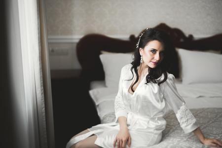 Foto de Gorgeous bride in robe posing and preparing for the wedding ceremony face in a room - Imagen libre de derechos