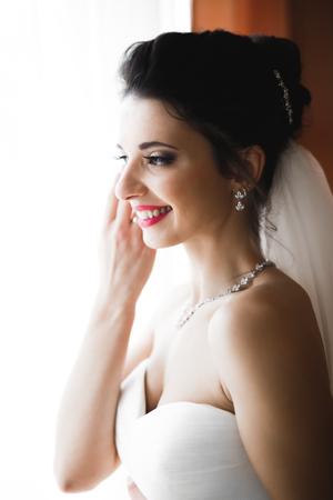 Foto de Luxury bride in white dress posing while preparing for the wedding ceremony - Imagen libre de derechos