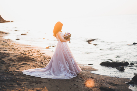 Foto per Portrait of stunning bride with long hair posing with great bouquet - Immagine Royalty Free