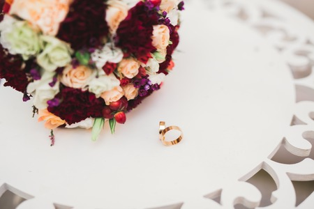 Foto de Beautiful toned picture with wedding rings against the background of a bouquet of flowers - Imagen libre de derechos