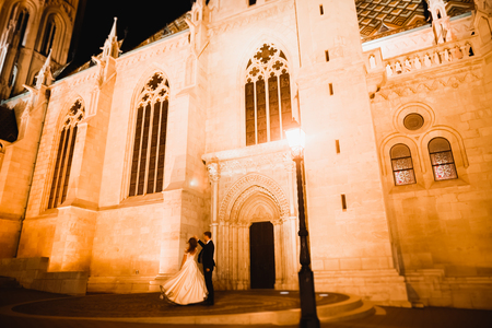 Foto de Beautiful bride spinning with perfect dress near great historical building - Imagen libre de derechos