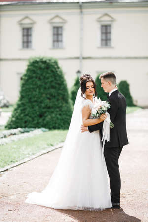 Photo for Wedding couple on the nature is hugging each other. Beautiful model girl in white dress. Man in suit - Royalty Free Image