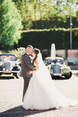 Photo pour Happy newlywed couple, man and wife kissing near stylish retro car - image libre de droit
