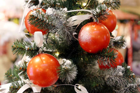 Photo pour Christmas tree with decorations, New Year celebration. Orange toy balls on a branch on blurred lights background - image libre de droit