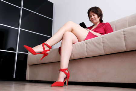 Photo pour Woman in red shoes on high heels sitting on a sofa and using smartphone. Concept of online addiction, sms or flirting - image libre de droit