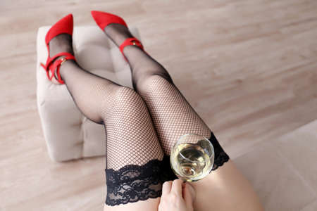 Photo pour Woman in black fishnet stockings sitting with a glass of white wine. Drunk hot girl, concept of celebration, home relax, romantic date - image libre de droit