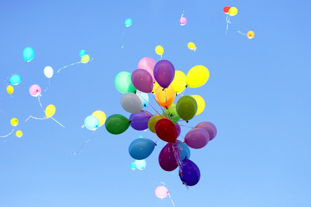 Photo pour many multicolored balloons flying in the blue sky. Items to celebrate events  - image libre de droit