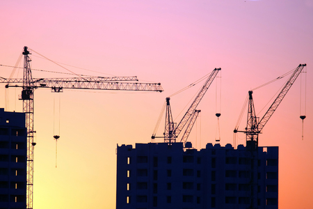 Photo for Construction cranes with built houses on the background of the sunset sky. industrial construction industry - Royalty Free Image