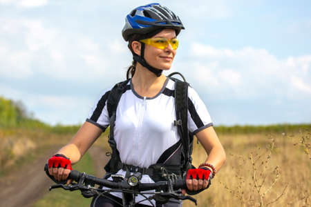 Photo pour Beautiful and happy girl cyclist with a bike on nature. Healthy lifestyle and sports. Leisure and hobbies - image libre de droit