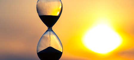 Foto de Hourglass counts the length of time against the background of the evening sun - Imagen libre de derechos