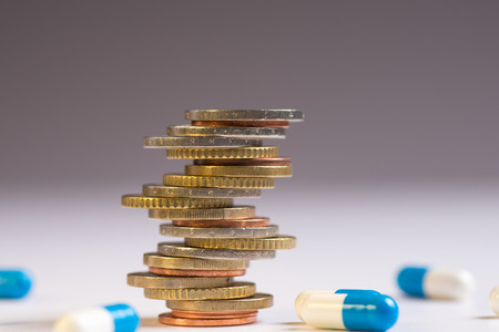 Foto de Coins are placed among themselves in different positions next to the blue and white pills. Copy space for text - Imagen libre de derechos