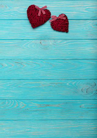 Photo pour Valentine's Day. Decorative wicker hearts of burgundy color on azure wood background. Selective focus. - image libre de droit