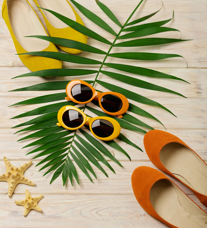 Beach accessories - sunglasses, hat and shoes orange and yellow color with tropical palm leaves wooden background with empty space for text. Flat lay, top view.