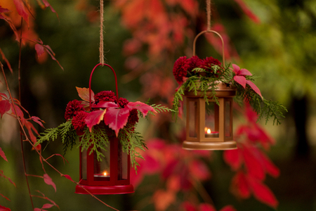 Photo pour Fall time. Autumn decoration. Candlesticks in the form of lanterns with daisy decor, juniper and autumn red leaves. Selective focus. - image libre de droit