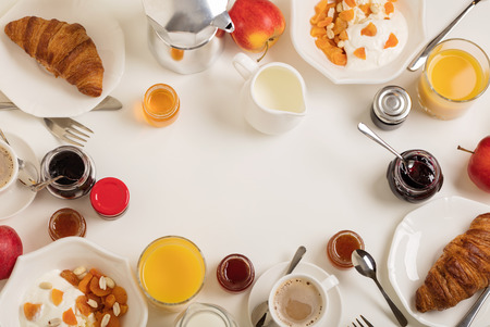 Foto de Breakfast time. Croissants and orange juice, jam and honey. Coffee with cream or milk. Fruits - bananas, red and green apples. Ricotta with sour cream, nuts and dried apricots. Breakfast on a white table. View from above. - Imagen libre de derechos
