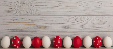 Foto de Happy Easter! Painted Easter eggs - red, white and red with white polka dots on a gray wooden background. Selective focus. - Imagen libre de derechos