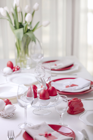 Photo for Happy easter. Decor and table setting of the Easter table is a vase with white tulips and dishes of red and white color. Easter colored eggs with white polka dots. Selective focus. - Royalty Free Image