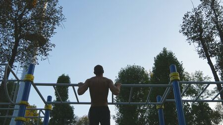 Strong muscular man doing pull ups in a park. Young athlete doing chin-ups on horizontal bars outdoor. Silhouette of fitness muscular man training outside in summer. Workout sport lifestyle. Rear view