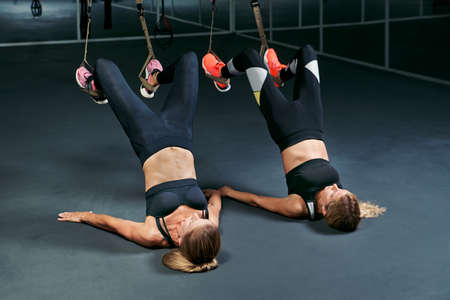 two athletic women doing sling exercises in the gym.