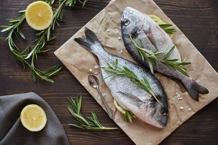 Photo pour Fresh uncooked dorado or sea bream fish with lemon, herbs, oil, vegetables and spices on rustic wooden board over black backdrop, top view - image libre de droit