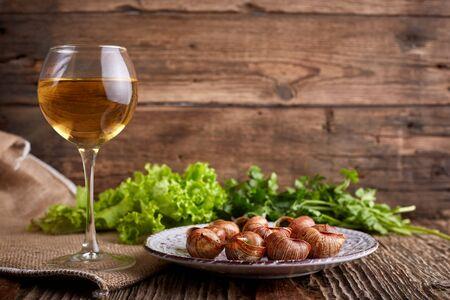 Photo pour Escargots de Bourgogne - Snails with herbs butter on wooden background. Salad. Parsley. Glass of wine. - image libre de droit