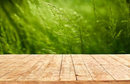 Foto de Mockup. Empty wooden deck table with foliage bokeh background. - Imagen libre de derechos