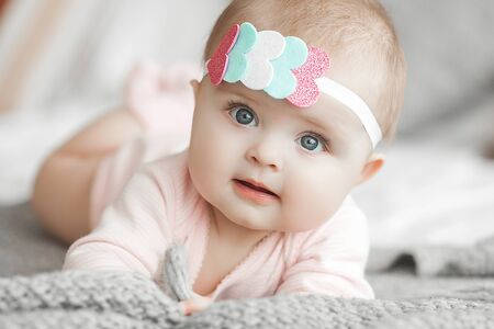 Photo pour Cute litttle baby at home in the bedroom. An infant indoors. 6th month child portrait. Adorable cute baby girl. - image libre de droit