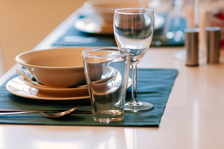 Photo pour Close up dining setup with empty wine and water glasses, silver cutlery and blue napkins, decorations and items served for food, arranged by catering service in a modern restaurant, cafe - image libre de droit