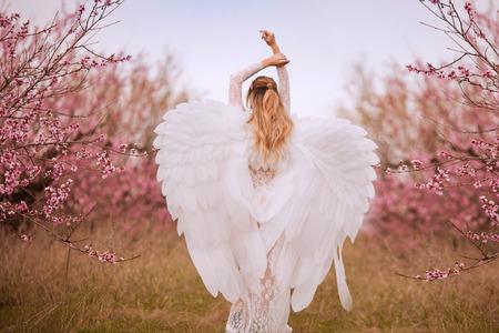 Foto de Beautiful yound woman with giant white angel wings - Imagen libre de derechos