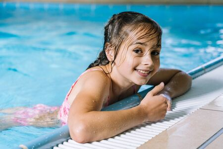 Photo pour Portrait girl having fun in indoor swimming-pool. The girl is resting at the water park. Active happy kid. Swimming school for small children. Concept friendly family sport and summer vacation. - image libre de droit