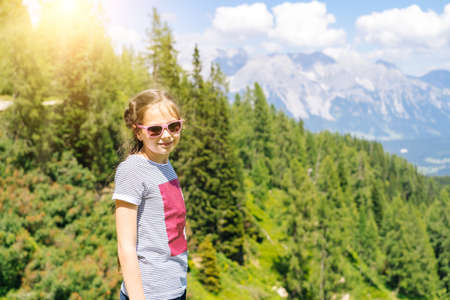 Photo for Girl hiking on beautiful summer day in alps mountains Austria, resting on rock and admire amazing view to mountain peaks. Active family vacation leisure with kids.Outdoor fun and healthy activity. - Royalty Free Image