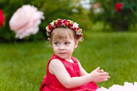 Photo pour Little girl in red dress playing  on the green lawn with high artificial rose flowers on background. Springtime, blossom and childhood concept. - image libre de droit