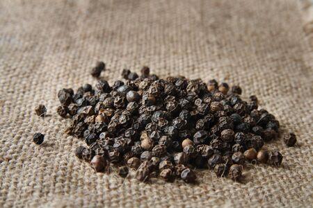 pile of black pepper on a burlap canvas