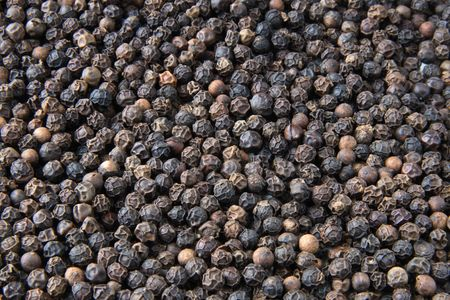 Whole black pepper close-up background