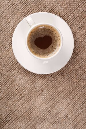 Cup of black coffee on hessian background,