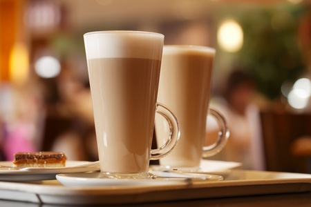 coffee latte in two tall glasses inside, shallow dof