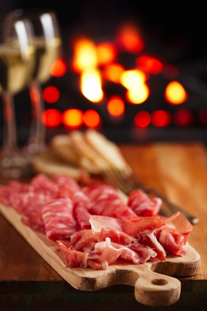 Platter of serrano jamon Cured Meat with cozy fireplace and wine backgroundの写真素材