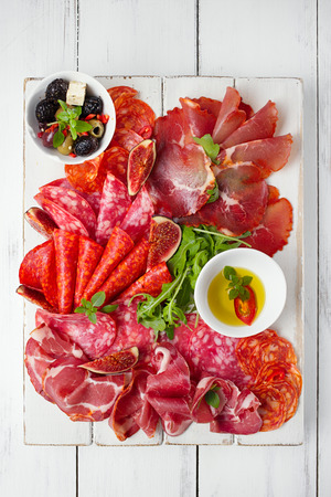 antipasti Platter of Cured Meat,   jamon, sausage, salame  on textured white wooden tableの写真素材