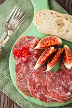 meat platter of Cured Meat and figs on green wooden boardの写真素材