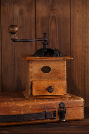 Nostalgic coffee grinder on old stool and textured wood background