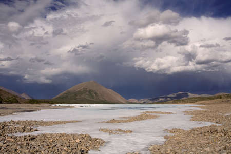Remains of ice in the valley of the mountain river and beautiful clouds. Ridge Suntar-Hayata. Yakutia. Russia.